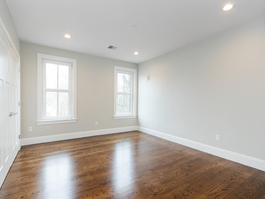 Another empty bedroom with two windows at the end.