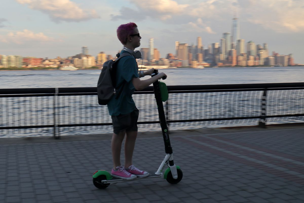 A woman wearing a backpack rides an e-scooter along a waterfront pathway with the New York City skyline in the background.