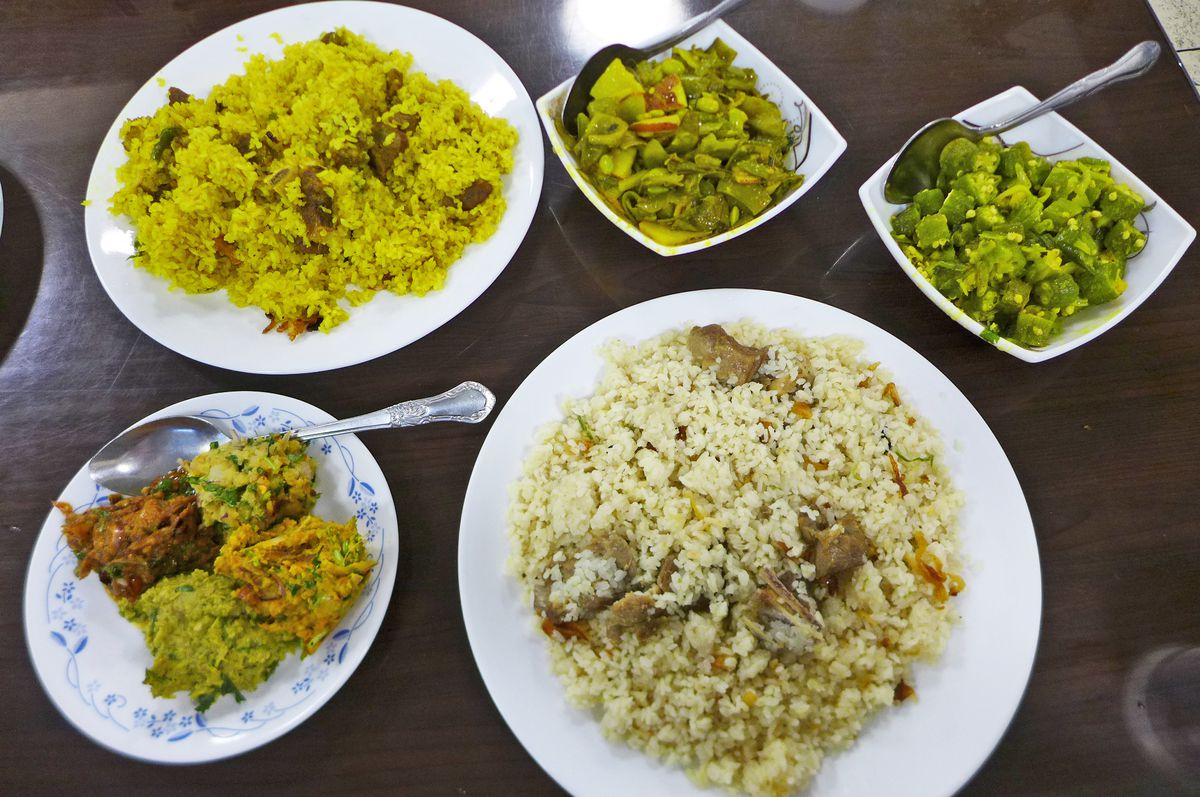 A selection of rice and vegetable dishes in white bowls.