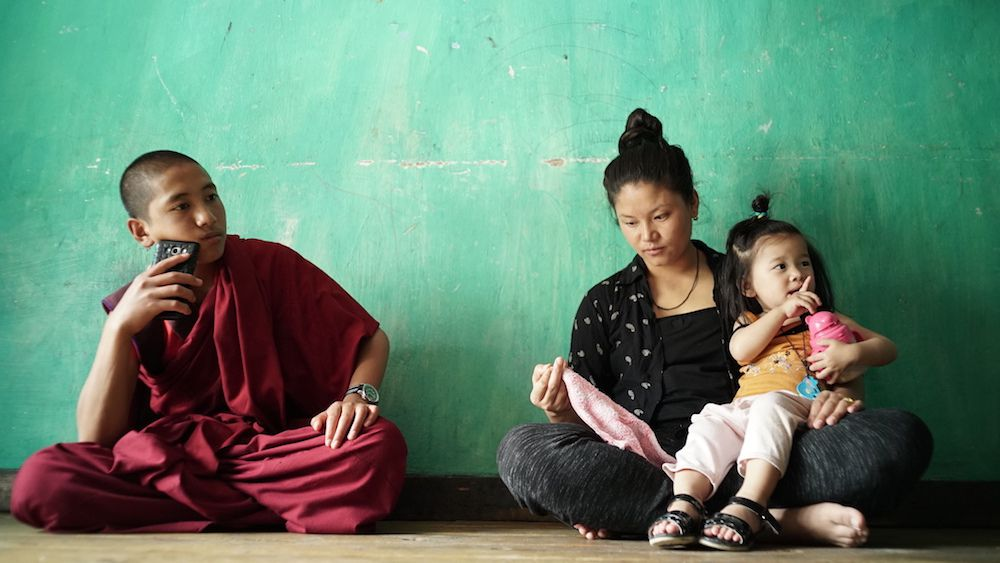 Young Buddhist monk Peyangki sits near a young woman and her child — his romantic interest — in Sing Me a Song.