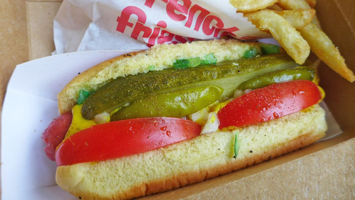 A hot dog with the sausage barely visible, topped with many green, red, and yellow ingredients.
