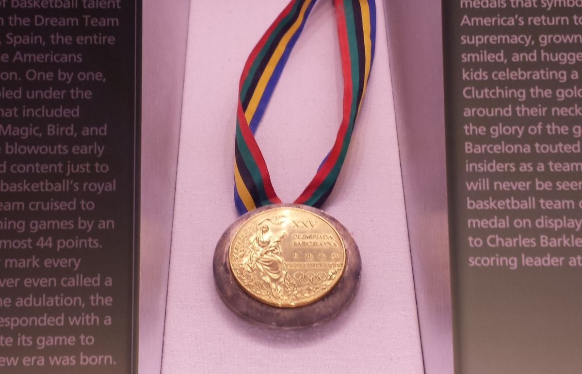 Gold medal hanging from a rainbow ribbon