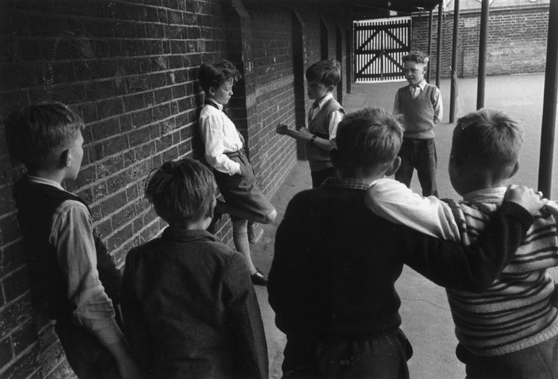 Children bullying a boy in a playground.