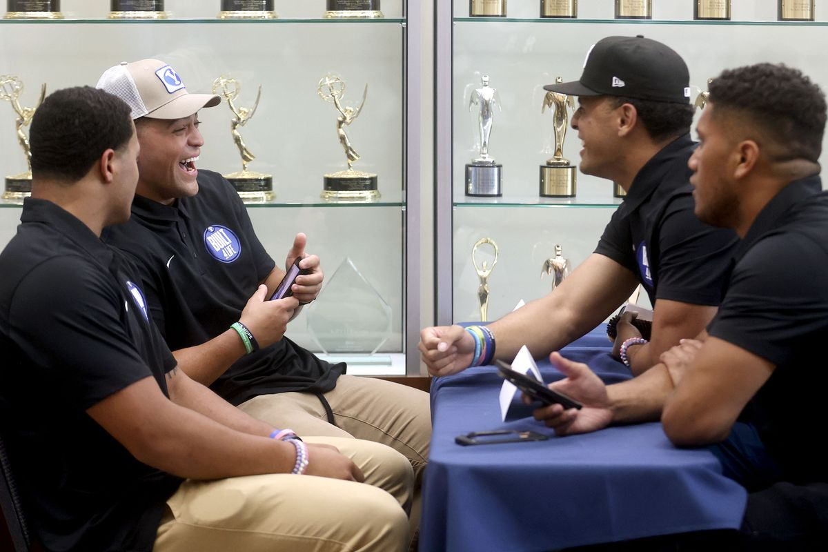 BYU running back Lopini Katoa, back left, laughs while chatting with teammates during BYU football media day.