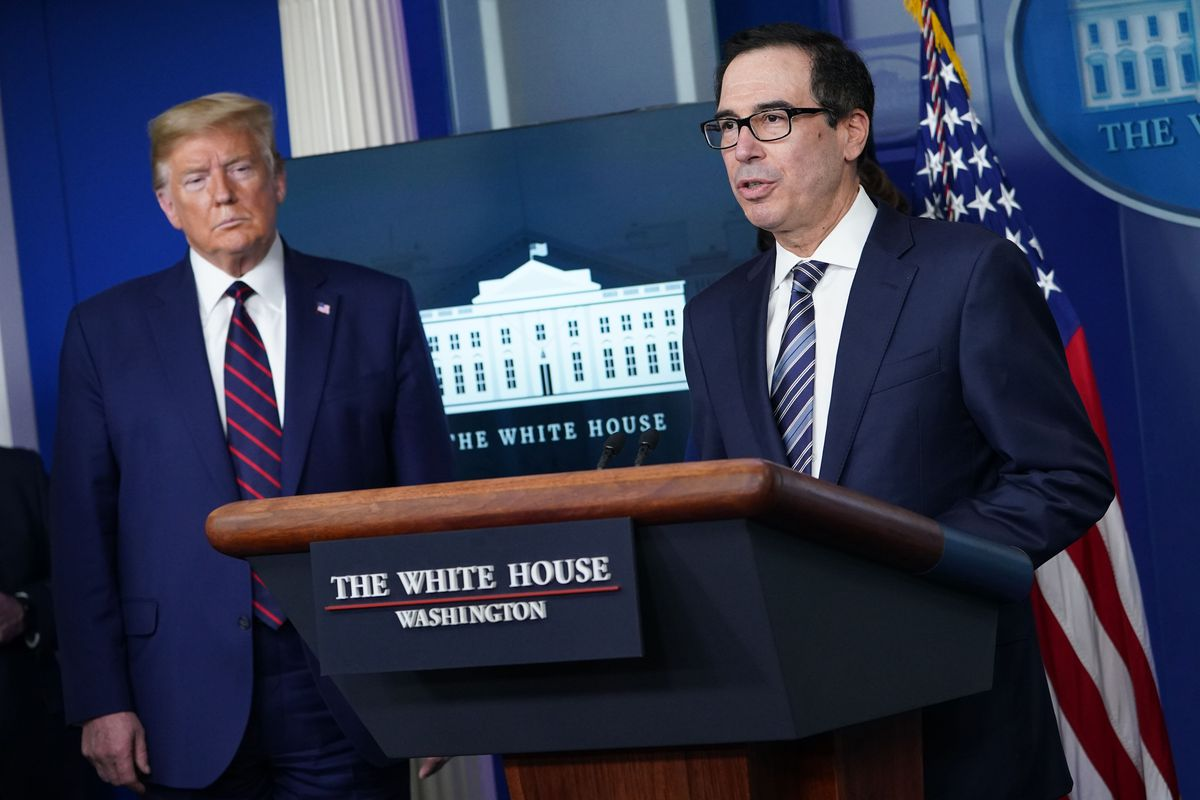 U.S. Treasury Secretary Steve Mnuchin stands next to President Donald Trump at a White House press conference