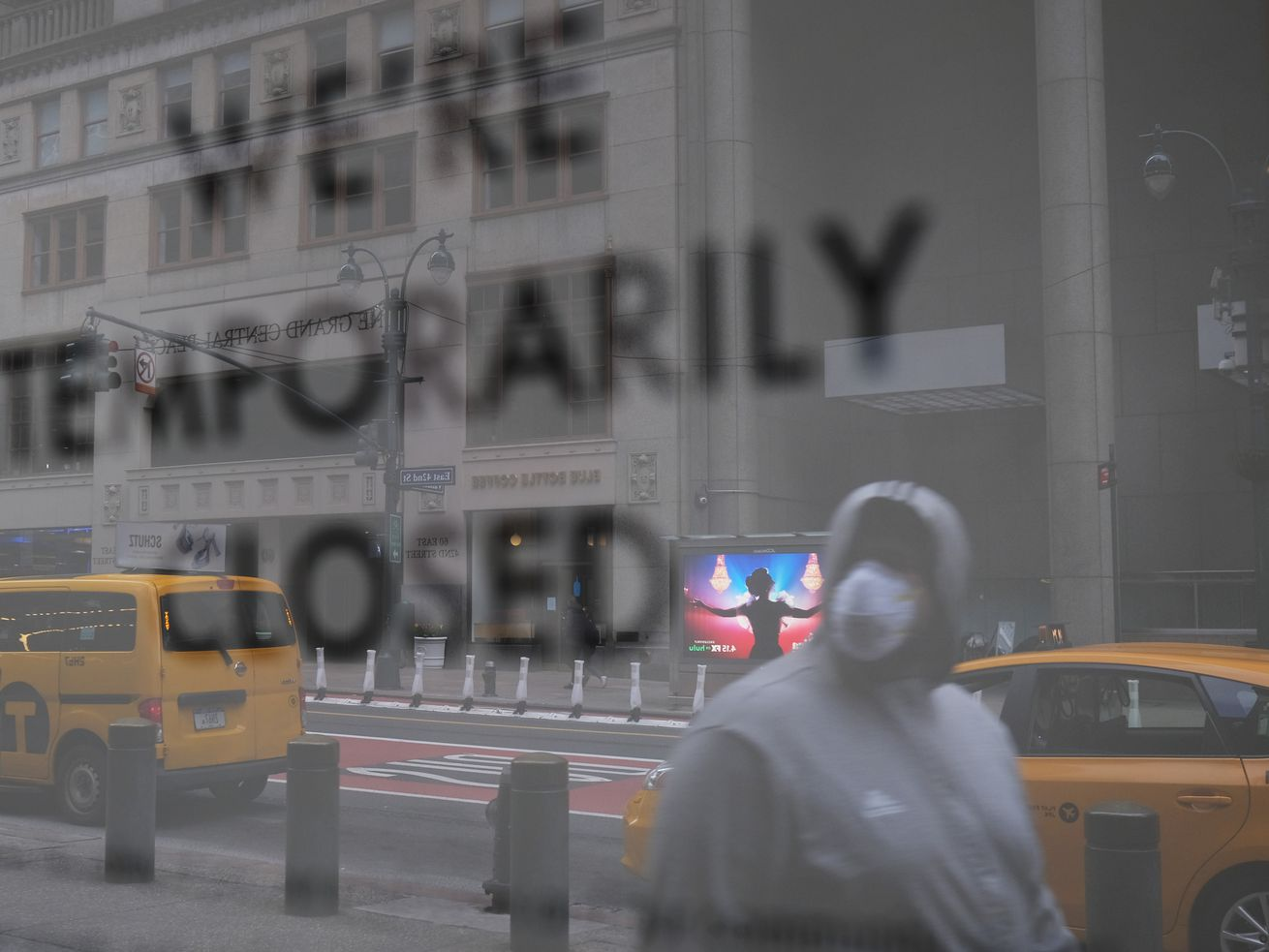 "A man in a mask walking by a storefront that reads ""We're temporarily closed."""