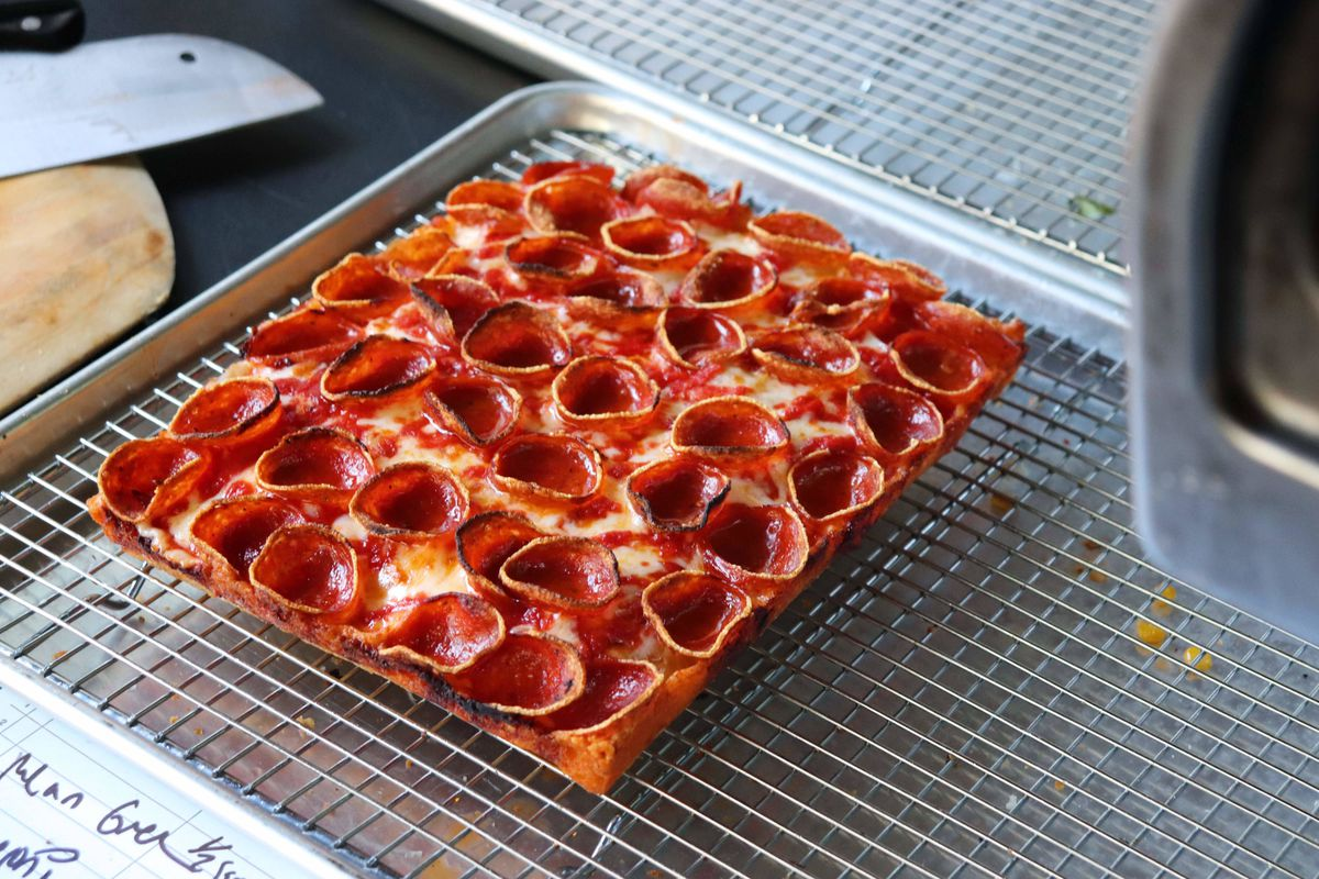 A slab of Detroit-style square pizza with pepperoni cups