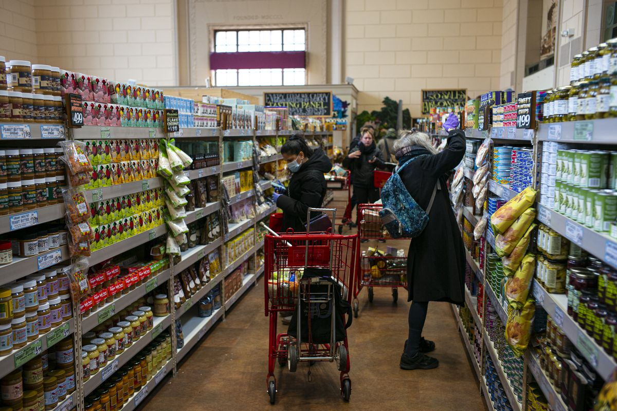 Shoppers wearing surgical masks and latex gloves look at canned items at a Trader Joe's on April 3, 2020 in the Brooklyn borough of New York City.