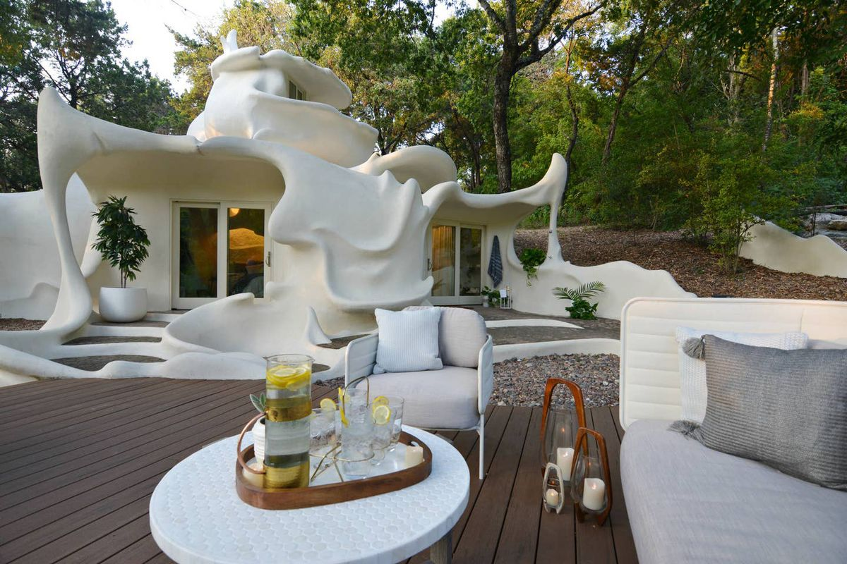 """A unique, sculptural """"organic modern"""" house with flowy walls, roof, and window openings. In front is a gravel area with a modern couch and a small round table that has a pitcher of lemonade and glasses staged on it."""