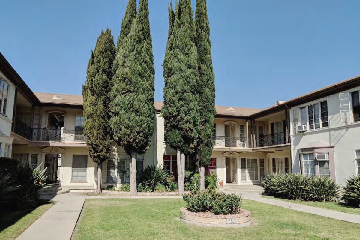 A photo of a green lawn surrounded on three sides by an apartment building. Tall cypress trees grow in a cluster at the far end of the lawn.