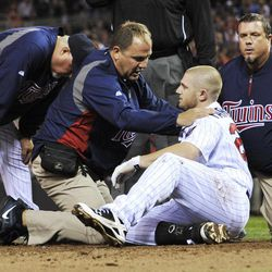 Minnesota Twins manager Ron Gardenhire, left, stands by as trainers attend to Chris Parmelee, who was hit in the helmet by a pitch from Boston Red Sox's Justin Thomas in the sixth inning of a baseball game Wednesday, April 25, 2012, in Minneapolis. Parmelee left the game.