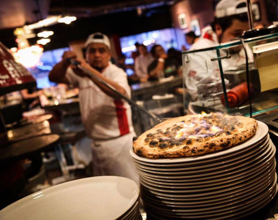 Removing a dessert pizza from the oven at Cane Rosso