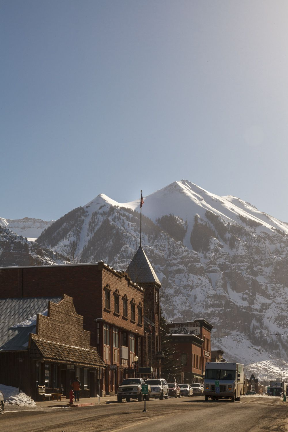 Looking up at mountains from the town of Telluride with buildings in the foreground.