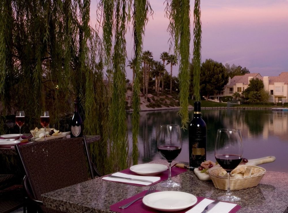 Table with bread and wine beside a lake
