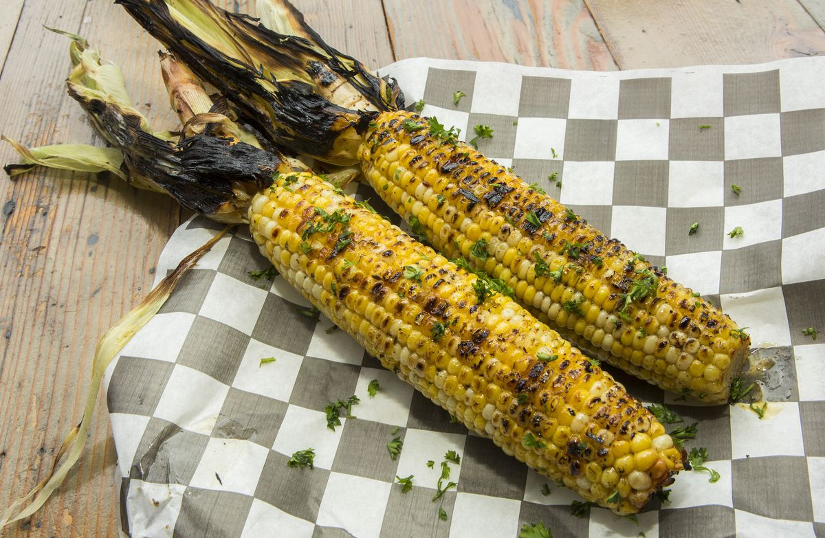 Two grilled corn cobs with charred husks on a plate with a paper wrapper.