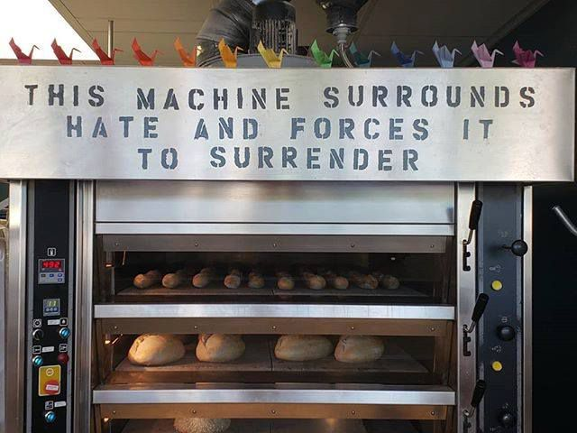 """A large commercial oven filled with bread. On the top of the oven it says, """"This machine surrounds hate and forces it to surrender."""""""