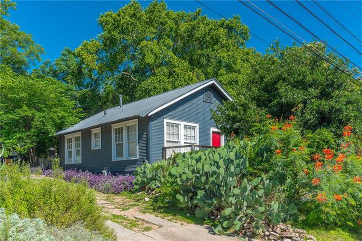 one-story frame house dark gray with red door, plants in front