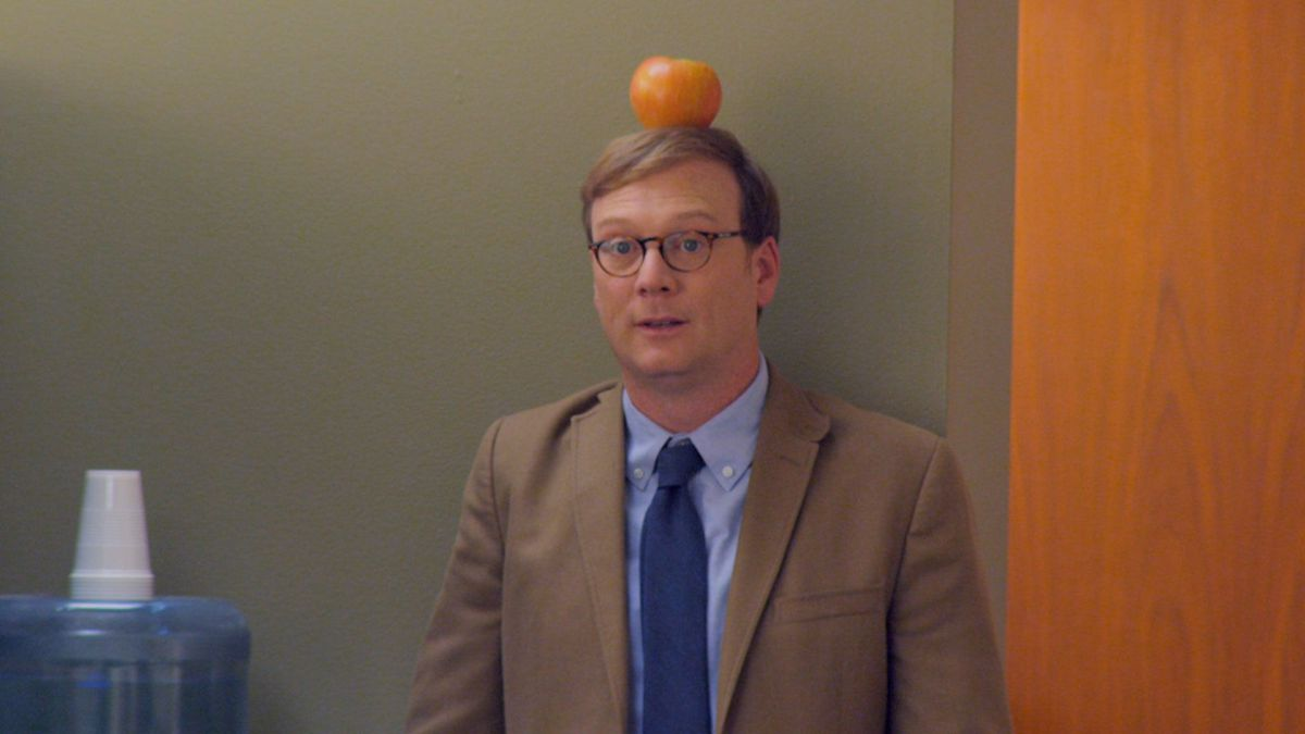 A man with an apple on his head.