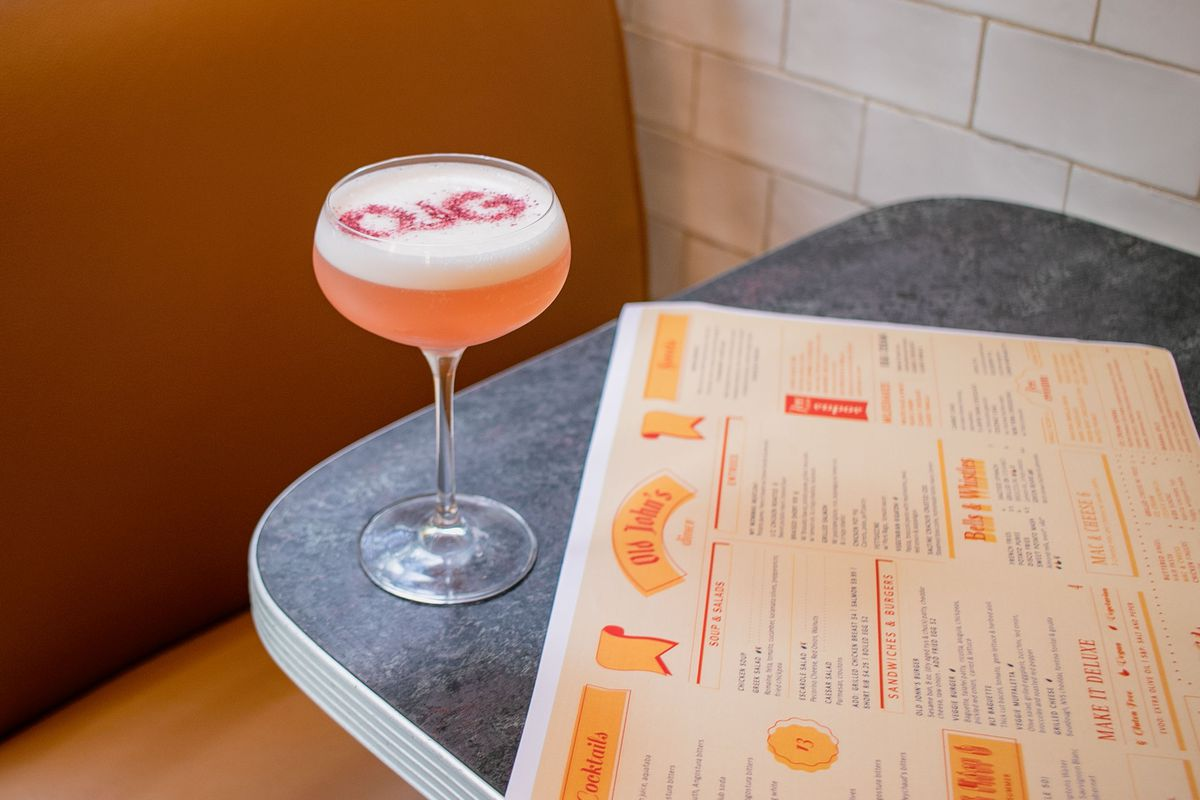 A long-stemmed glass with pink liquid and white foam sits on a blue and grey tabletop with a restaurant menu beside it and a brown booth in the background.