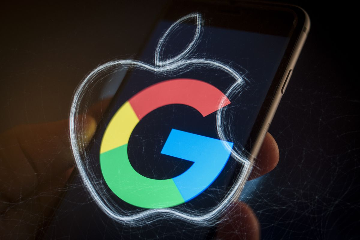 The Google G logo and the Apple logo superimposed on a smartphone held in a hand.