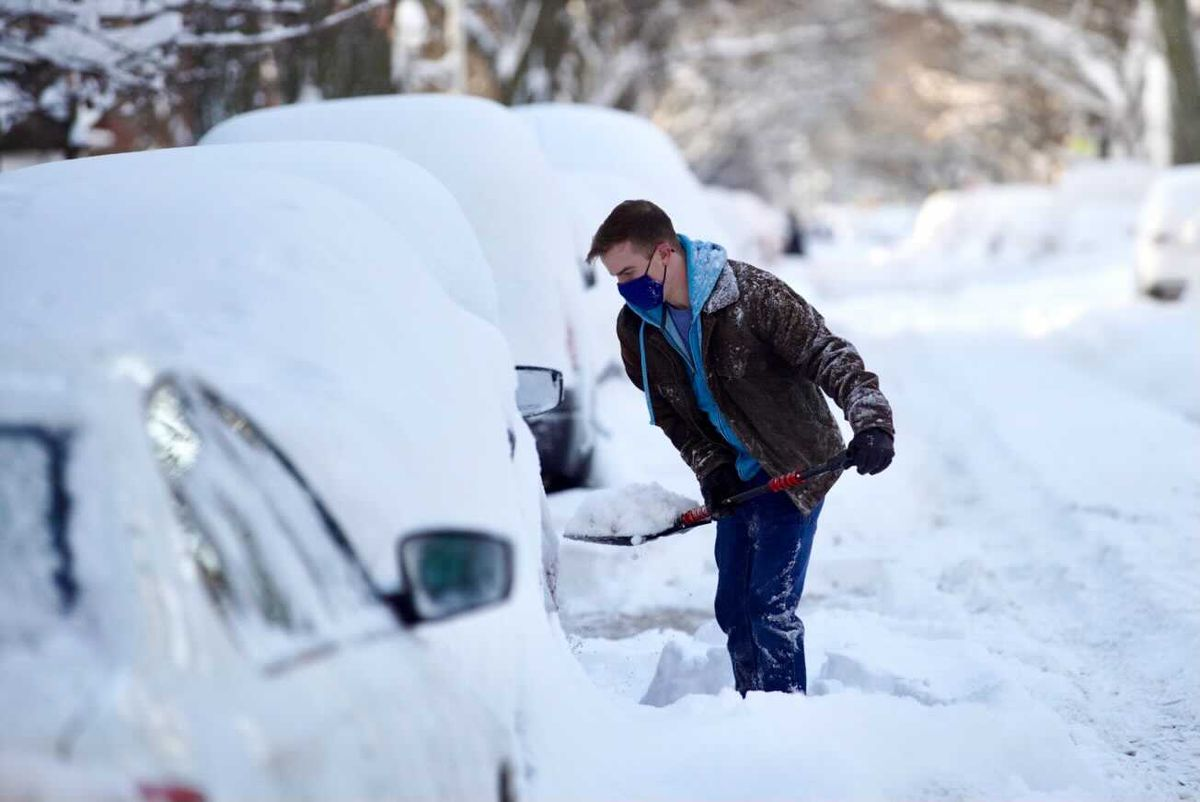 Michael Svabek tries to dig out a car Tuesday after parts of Chicago were buried under about 18 inches of snow.