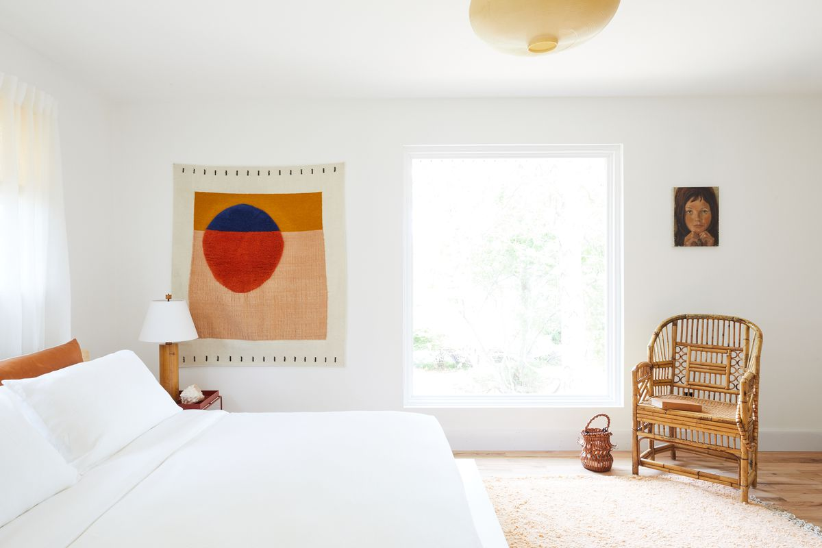 Bedroom with white walls and wicker chair