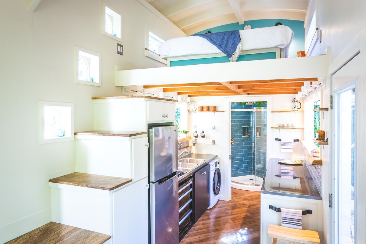 Interior of a tiny house with narrow staircase and a lofted bed over a kitchen.