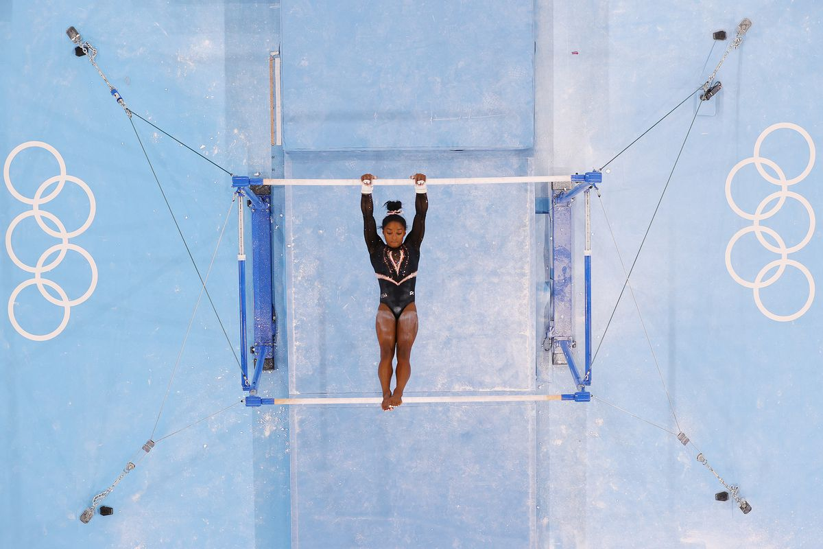 A gymnast on the uneven parallel bars, seen from above.