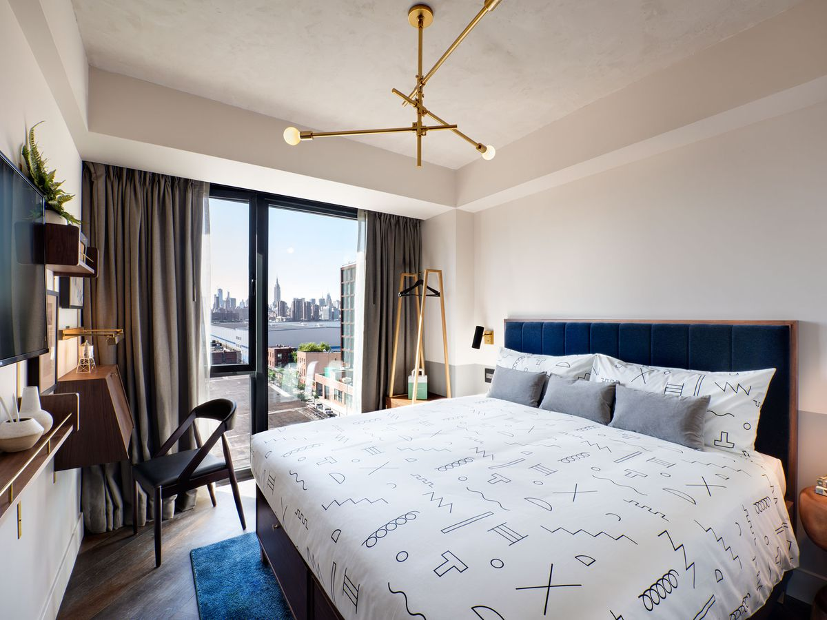 A guest room with a blue velvet headboard, concrete floors, and a view onto Williamsburg.