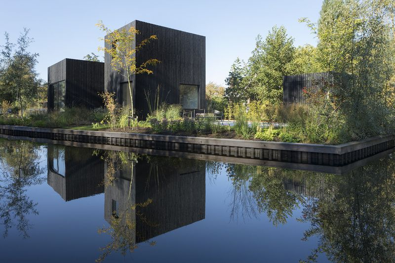 Black timber house on lake