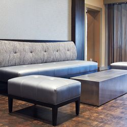new lounge area with silver furniture and silver textured wallpaper.