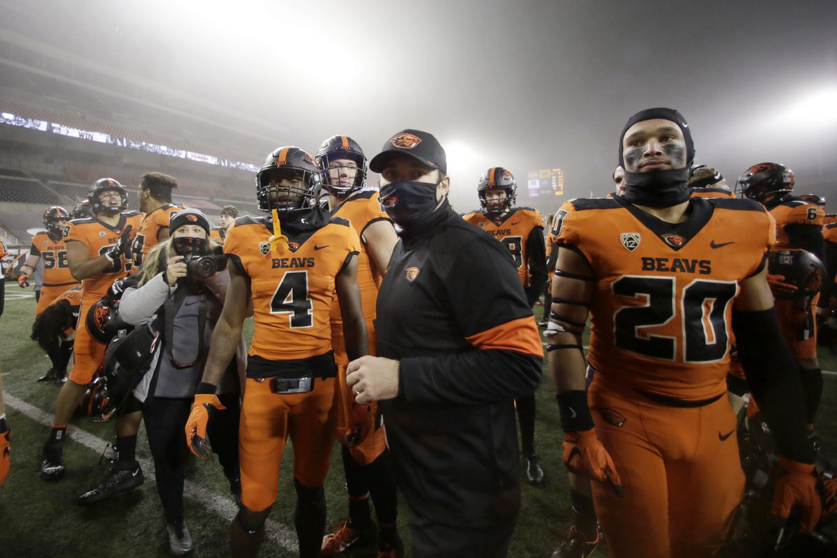 Oregon State Beavers players and head coach Jonathan Smith celebrate after defeating the Oregon Ducks at Reser Stadium.