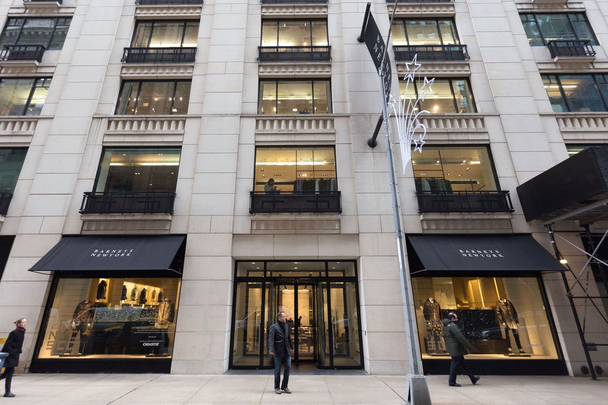 The exterior of a store in a large city building. There are multiple windows and on one of the window awnings are the words Barneys New York.