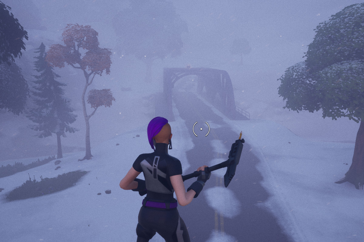 A Fortnite player stands in the middle of a blizzard looking out toward a barely visible bridge