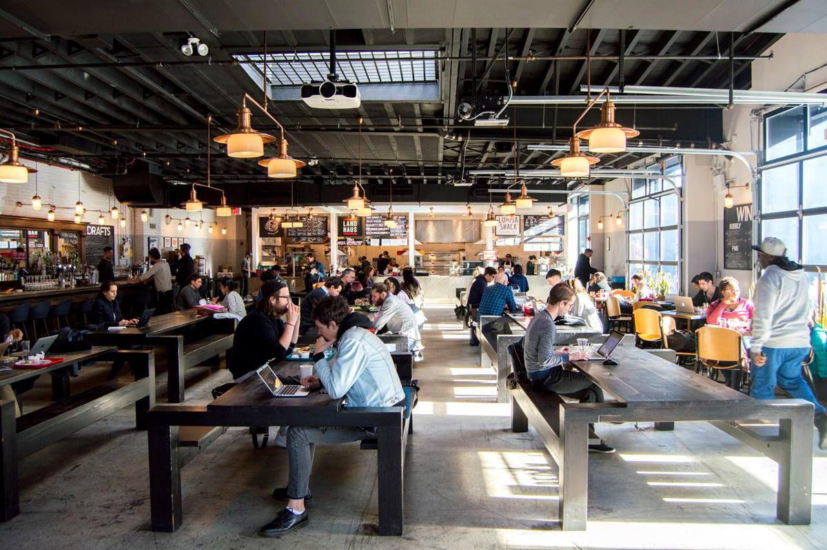 People sit at communal tables in a large space