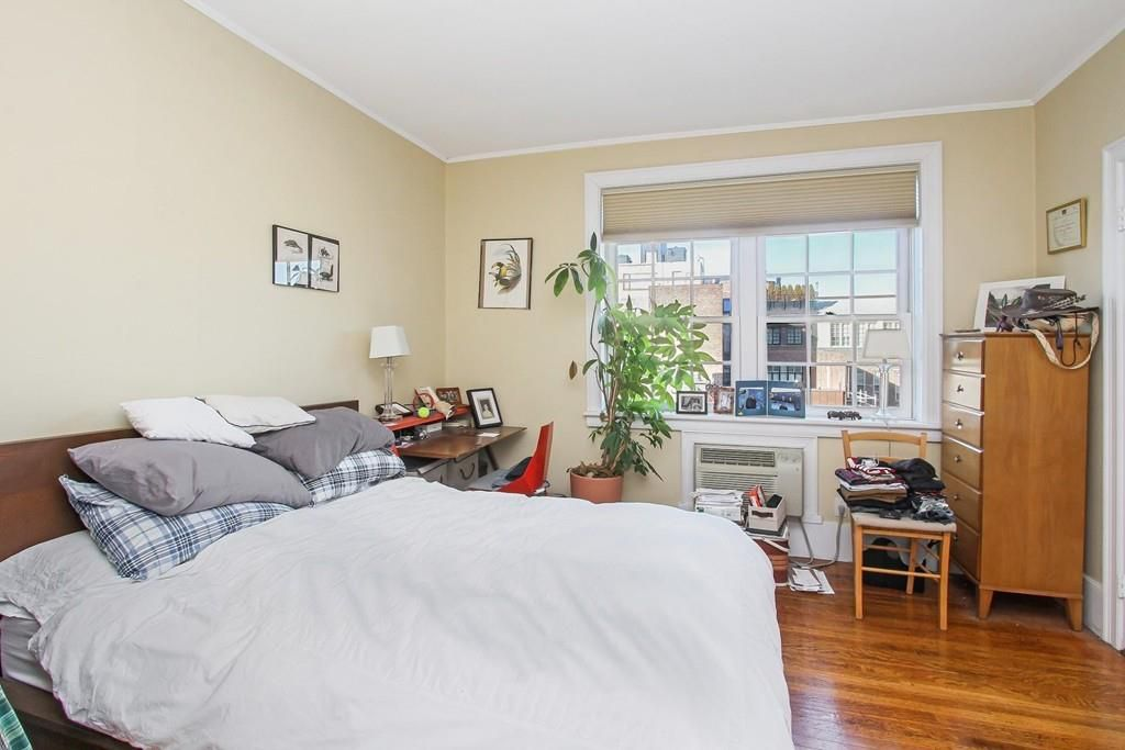 A sunny bedroom with a bed, a dresser, and a large window.