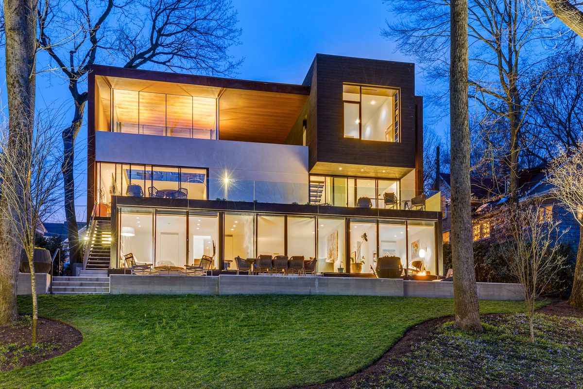 An exterior view of a boxy glass and steel home at night with the lights illuminated from the inside.