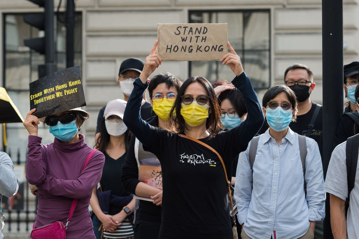 A crowd of people wearing facemasks hold up signs in support of Hong Kong.