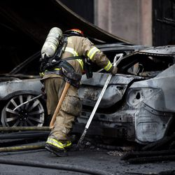 A South Salt Lake firefighter looks at vehicles damaged in an early morning fire at an apartment complex near 3300 South and 350 East in South Salt Lake on Thursday, April 16, 2020.