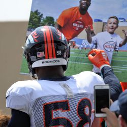 Broncos ILB Von Miller signs a poster from his football camp for a fan.