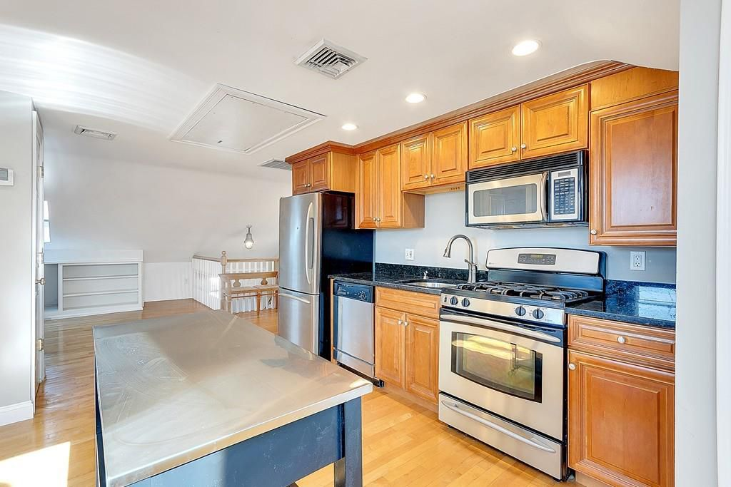 An open kitchen with one row of cabinets and counter, and an island.
