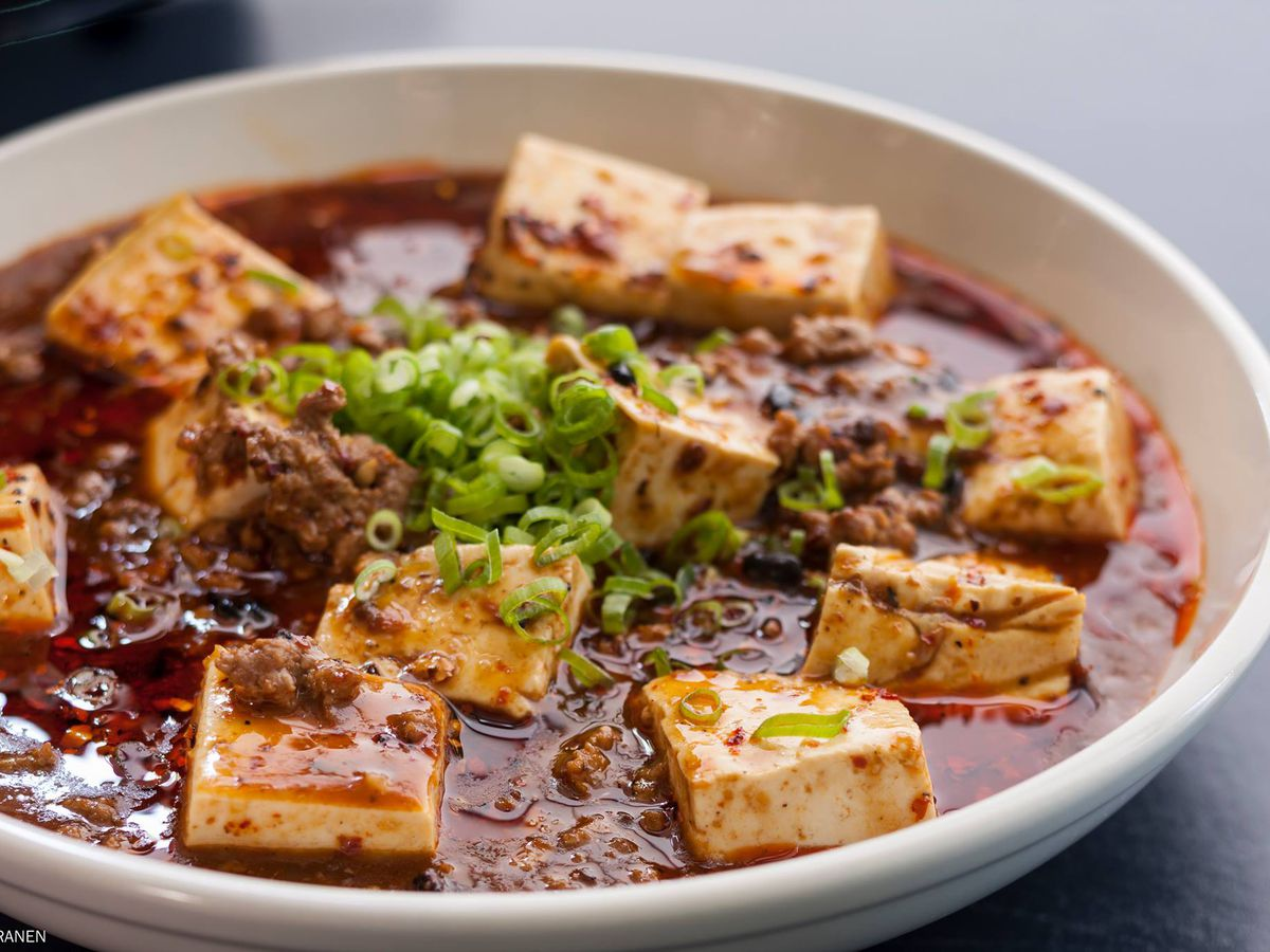 A closeup view of a bowl of tofu in red sauce topped with scallions at Lionhead.