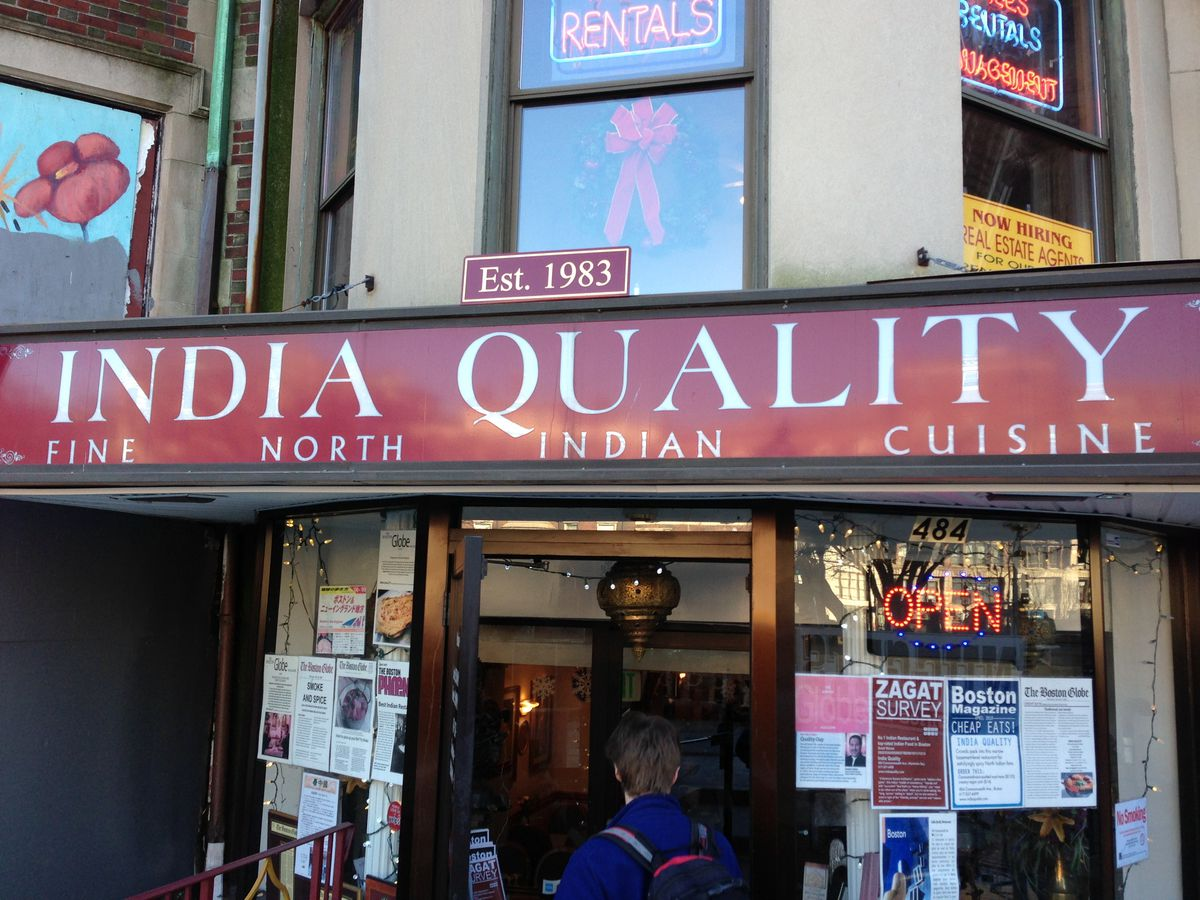"""The exterior of a restaurant. A large read sign says """"India Quality, Fine North Indian Cuisine, Est. 1983"""""""
