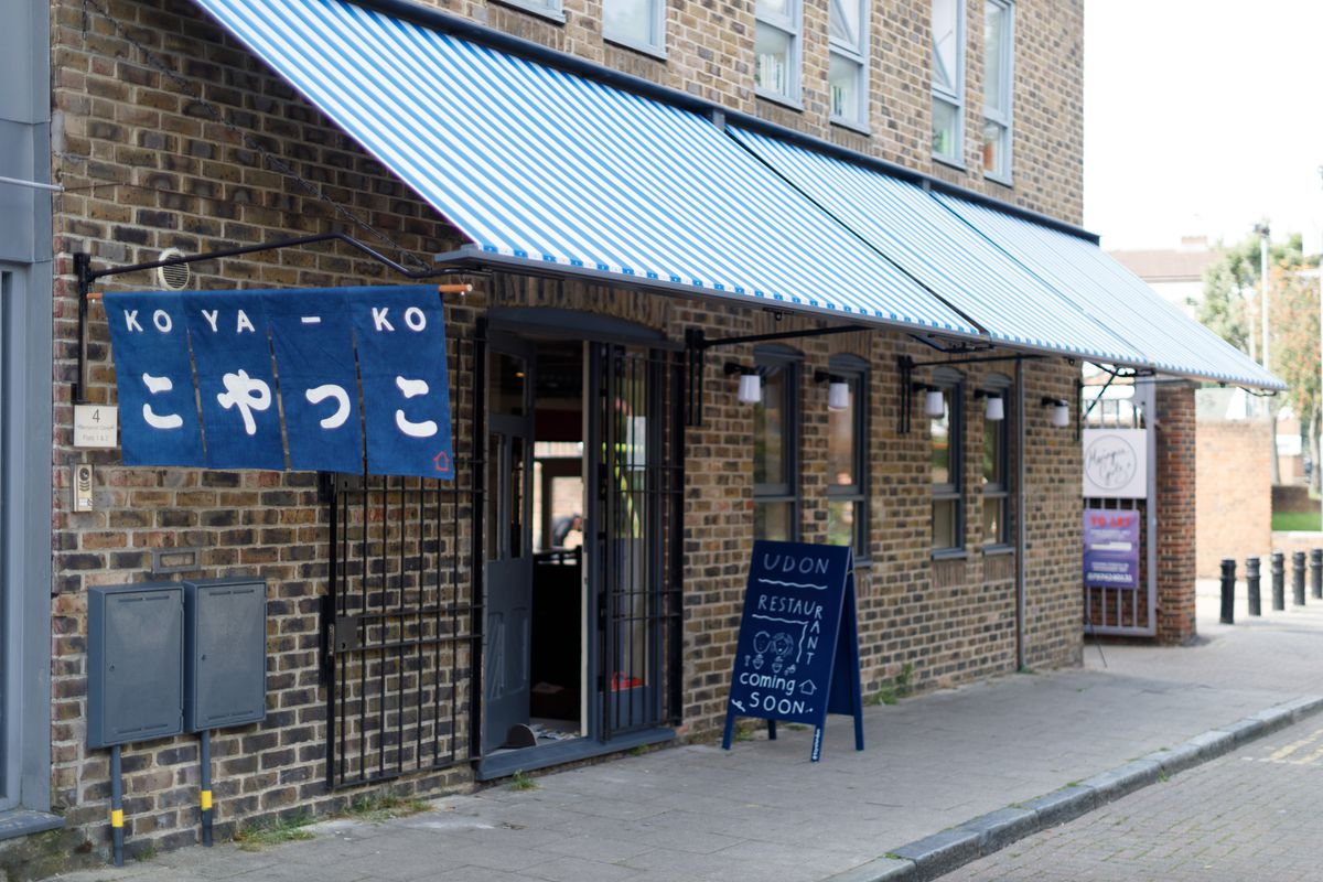 The outside of Koya Ko Broadway Market, with the name written in thick, white font in both English and Japanese on a denim-blue signage.