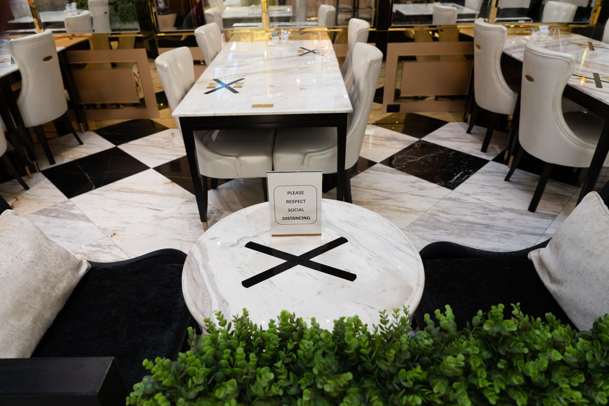 A white table at a restaurant with an X marked off in black tape