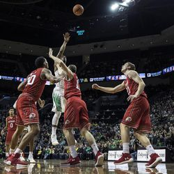 Oregon forward Mikyle McIntosh (22) shoots over Utah defenders during the first half in an NCAA college basketball game Friday, Dec. 29, 2017, in Eugene, Ore. (AP Photo/Thomas Boyd)