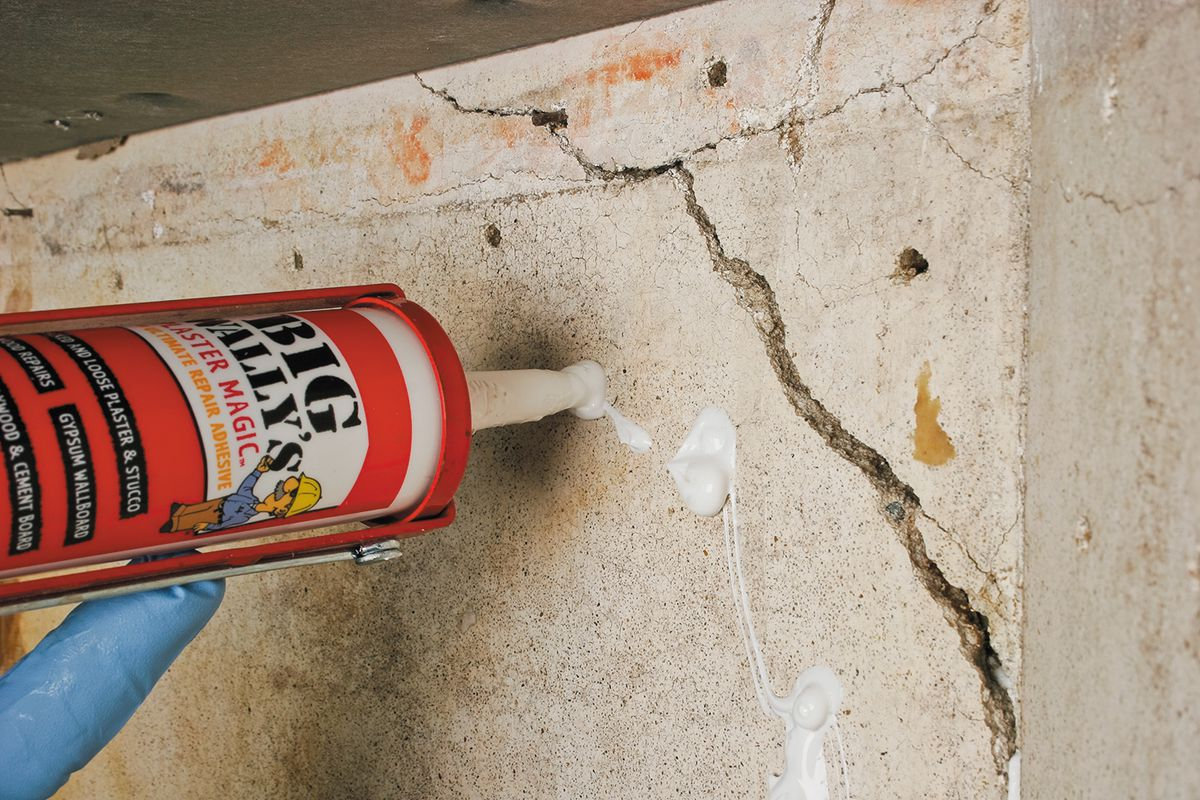 Man Injects Adhesive Into Primed Holes Of Plaster With Caulking Gun