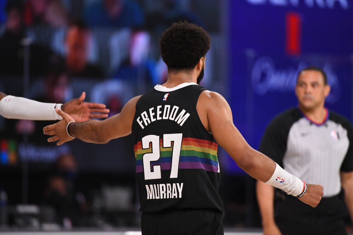 Jamal Murray of the Denver Nuggets hi-fives his teammate during the game against the Utah Jazz during Round One, Game One of the NBA Playoffs on August 17, 2020 in Orlando, Florida at The Field House.