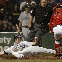 Toronto Blue Jays' Travis Snider is out sliding into home as Boston Red Sox catcher Jason Varitek and home plate umpire Gary Cederstrom look on.