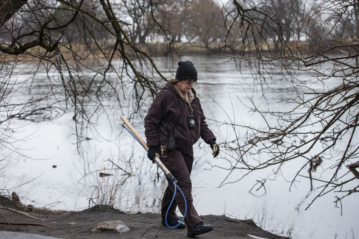An inspector from Chicago Animal Care and Control walks around the Peggy Notebaert Nature Museum in Lincoln Park, catch pole in hand, to look for a coyote den, Thursday morning, Jan. 9, 2020. Two people — including a 6-year-old boy bit multiple times near the museum — were attacked by a coyote in separate incidents Wednesday in Chicago.